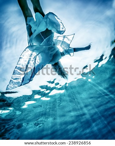Beautiful woman silhouette in the sea, sportive female swimming in transparent water, enjoying summer vacation, relaxation and pleasure concept - stock photo
