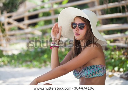 Beautiful woman sit on the sand at paradise beach - stock photo