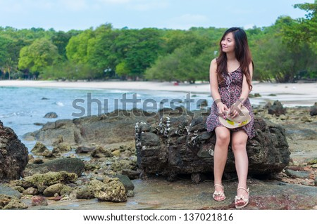 Beautiful woman sit on the stone, happy on a beach. - stock photo