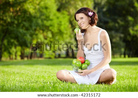 Beautiful woman sits and eats an apple on lawn, horizontally - stock photo