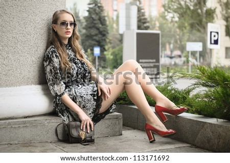 Beautiful woman sitting at column