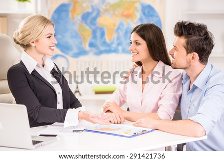 Beautiful woman sitting at office with clients and proposing hot tours to them. - stock photo