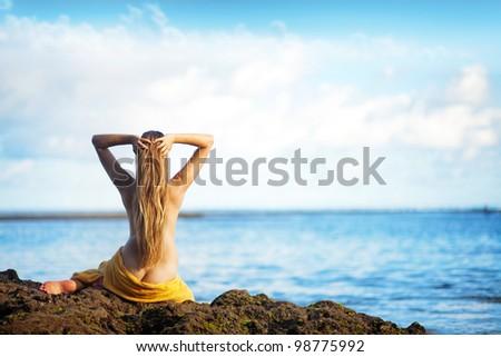 beautiful woman sitting from the back on beach, bali - stock photo
