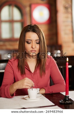 Beautiful woman sitting in a restaurant and drinking coffee