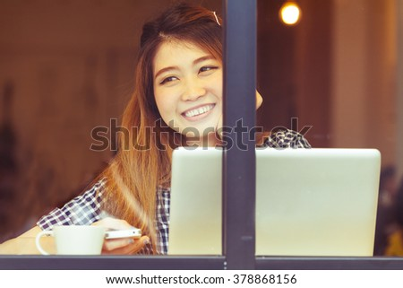 Beautiful woman sitting in coffee shop and happy to connecting by use technology computer laptop and contact with a cell phone when looking through the glass window in vintage color.