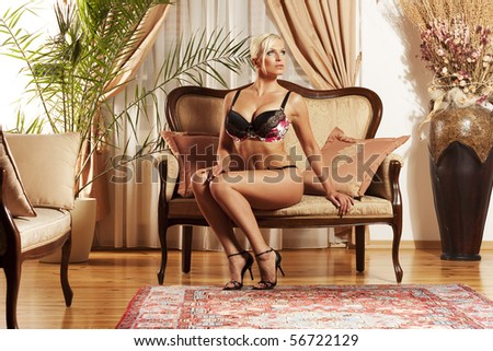 Beautiful woman sitting in luxury underwear in antique lounge - stock photo