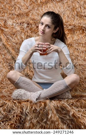 Beautiful woman sitting in Studio with fur background.