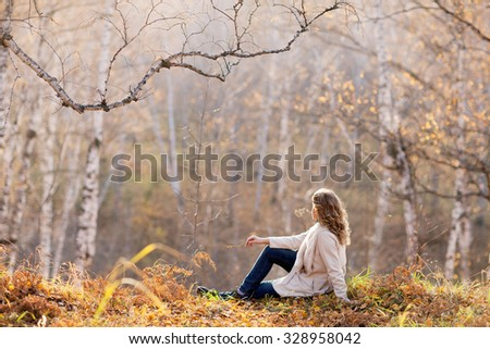 Beautiful woman sitting in the autumn forest