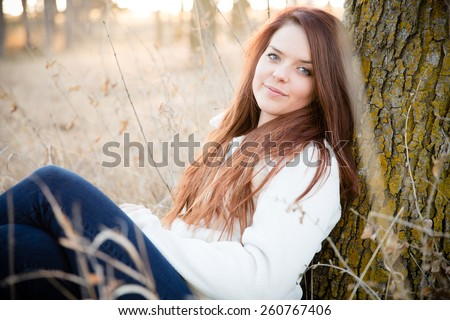 Beautiful Woman Sitting In The Park - This is a shot of a beautiful young woman sitting in some tall grass next to a tree enjoying the nice weather. Shot with a shallow depth of field. - stock photo