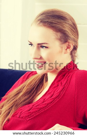Beautiful woman sitting on a couch and wearing red pullover. - stock photo