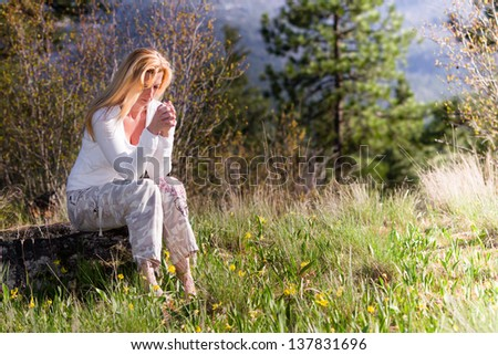 beautiful woman sitting on a rock praying with wild spring flowers around her - stock photo