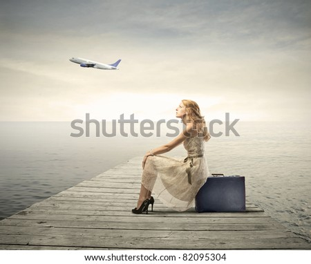 Beautiful woman sitting on a suitcase on a pier with airplane in the background