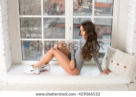 Beautiful woman sitting on a window sill