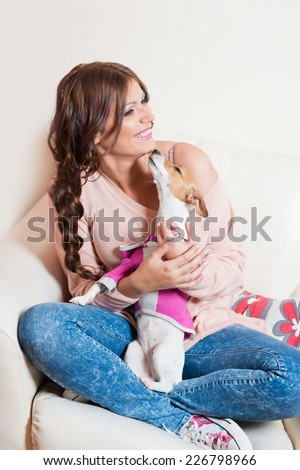 Beautiful woman sitting on an arm chair with a puppy - stock photo