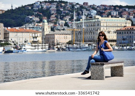Beautiful woman sitting on bench in harbour - stock photo