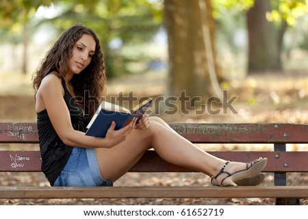 beautiful woman sitting on bench park reading book
