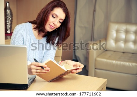 Beautiful woman sitting on her workout and looking in notebook at home - stock photo
