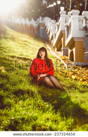 Beautiful woman sitting on hill at sunny autumn day - stock photo