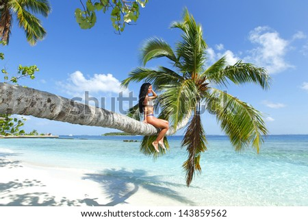 Beautiful woman sitting on palm on sea background - stock photo
