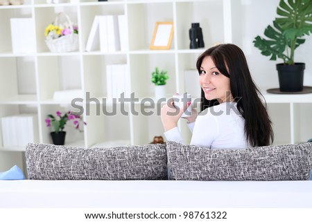 Beautiful woman sitting on sofa in living room and drinking tea - stock photo