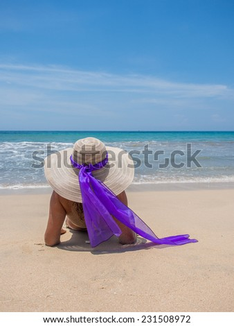 Beautiful woman sitting on the beach in Jambara Bali Indonesia
