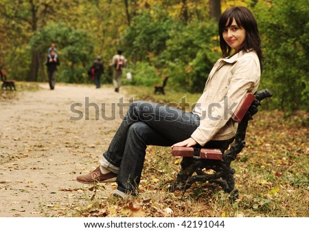Beautiful woman sitting on the bench in the park - stock photo
