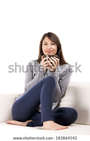 Beautiful woman sitting on the coach with a cup of coffee - stock photo