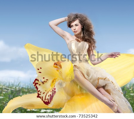 Beautiful woman sitting on the flower - stock photo