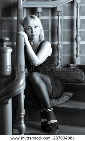 Beautiful woman sitting on the stairs and looking into the camera
