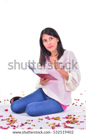 Beautiful woman sitting on the white floor while writing a letter surrounded by rose petals