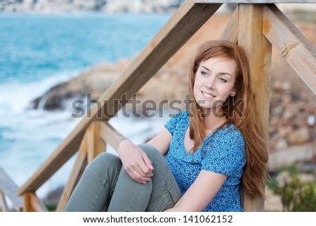 Beautiful woman sitting overlooking the sea on a rustic wooden staircase - stock photo