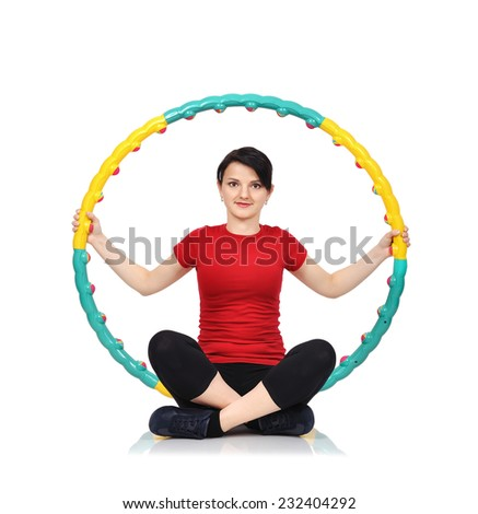 Beautiful woman sitting with color hula hoop - stock photo