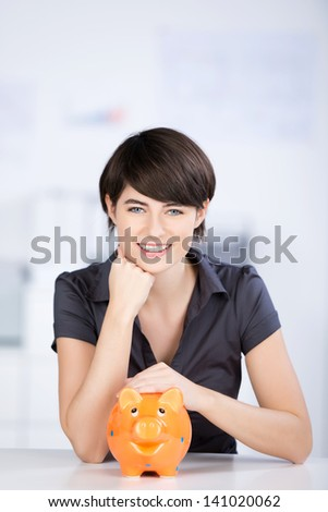 Beautiful woman sitting with piggybank over the white background - stock photo