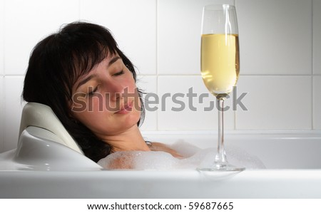 Beautiful woman sleeping in bath with glass of champagne - stock photo