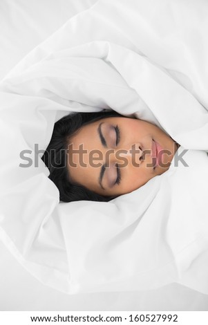 Beautiful woman sleeping lying under cover on her bed in bright bedroom