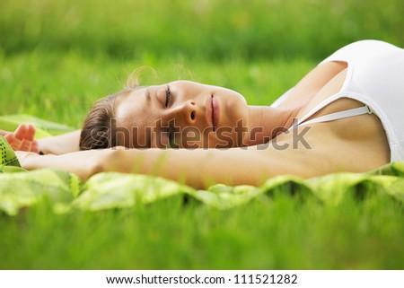 Beautiful woman sleeping on the grass - stock photo