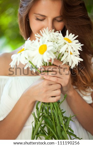 Beautiful woman smelling a bouquet of daisies, which in her hands. Close-up - stock photo