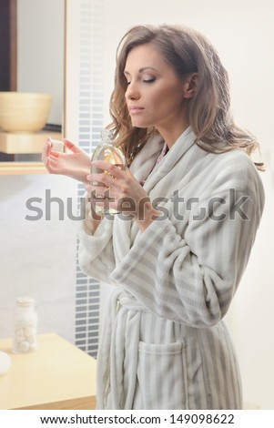 Beautiful woman smelling her perfume - stock photo