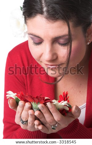 Beautiful woman smelling the flowers in her hands with her eyes closed - stock photo