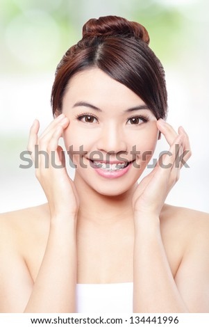 Beautiful woman smile face and finger touch her eyes with clean face skin, concept for eye and skin care, over nature green background, asian beauty - stock photo