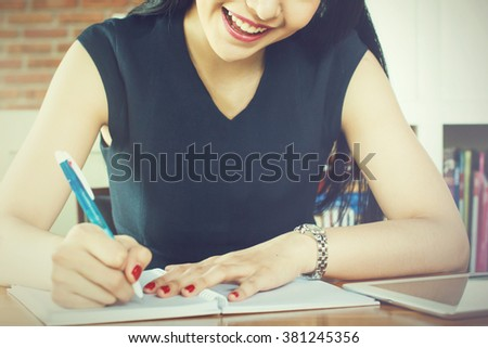 Beautiful woman smiling and writing a notebook on table (Focus on Mouth) - stock photo