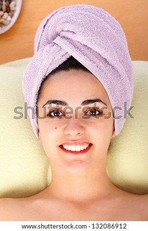 Beautiful woman smiling at spa with towel on her head.