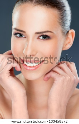 Beautiful woman smiling, close up over a dark  background