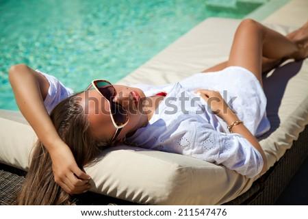 Beautiful woman smiling lying on sun chaise lounge near luxury pool side. Young woman enjoying summer vacation. - stock photo