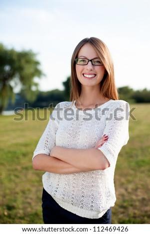 Beautiful woman smiling outdoors wearing glasses - stock photo