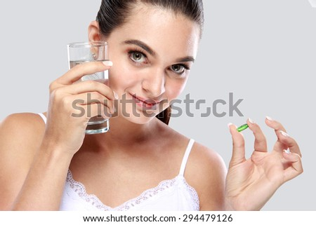 beautiful woman smiling while holding a glass of water and vitamin capsule for skin care