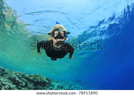 Beautiful Woman Snorkels over a Tropical Coral Reef - stock photo