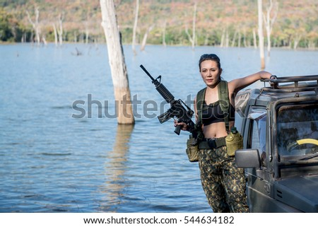 Beautiful woman soldier holding a rifle standing on a car. near reservoir