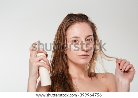 Beautiful woman spraying hairspray isolated on a white background - stock photo