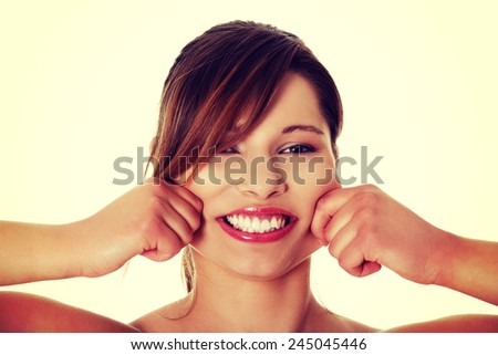 Beautiful woman spread smile to be wider. - stock photo
